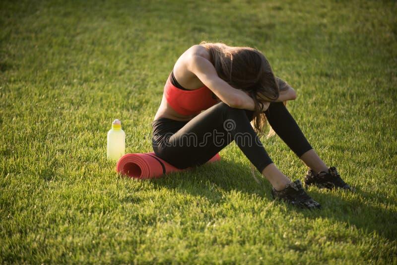 De vermoeide vrouw in sportkleding ontspant na training, opleiding stock foto's