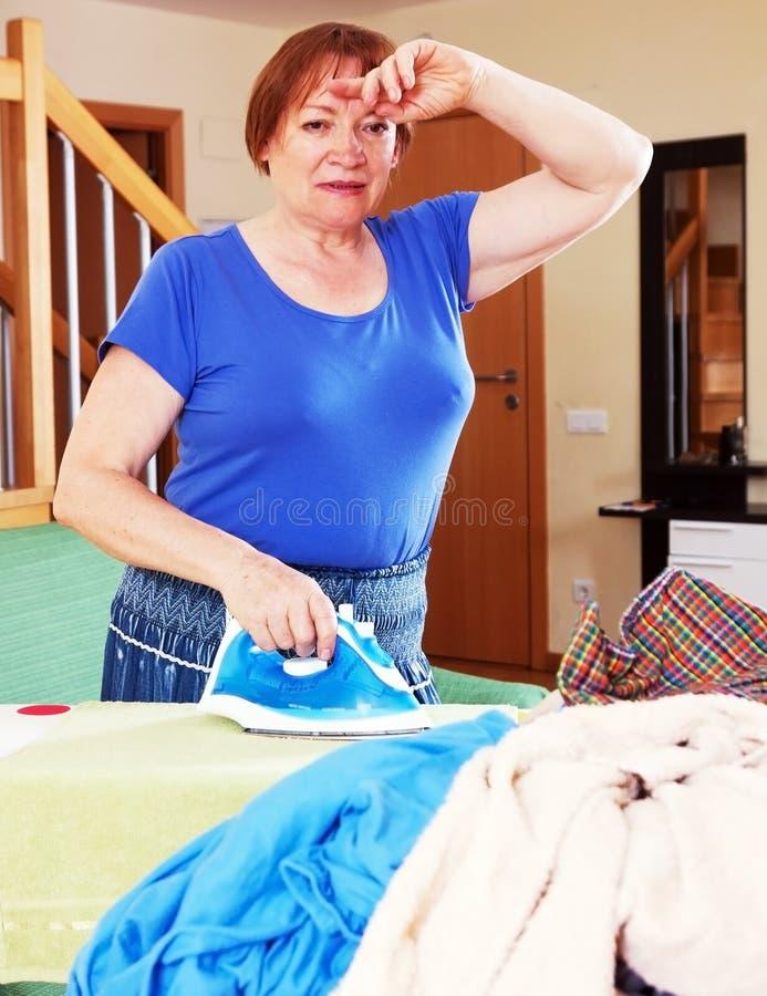 De vermoeide vrouw strijkt kleren royalty-vrije stock foto's
