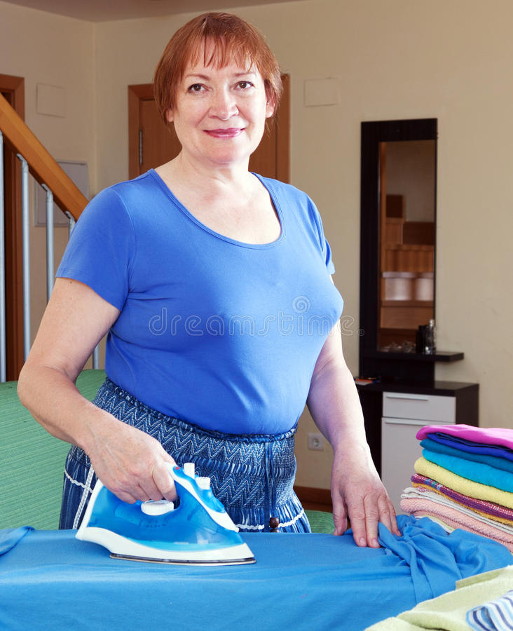 De vermoeide vrouw strijkt kleren royalty-vrije stock afbeeldingen