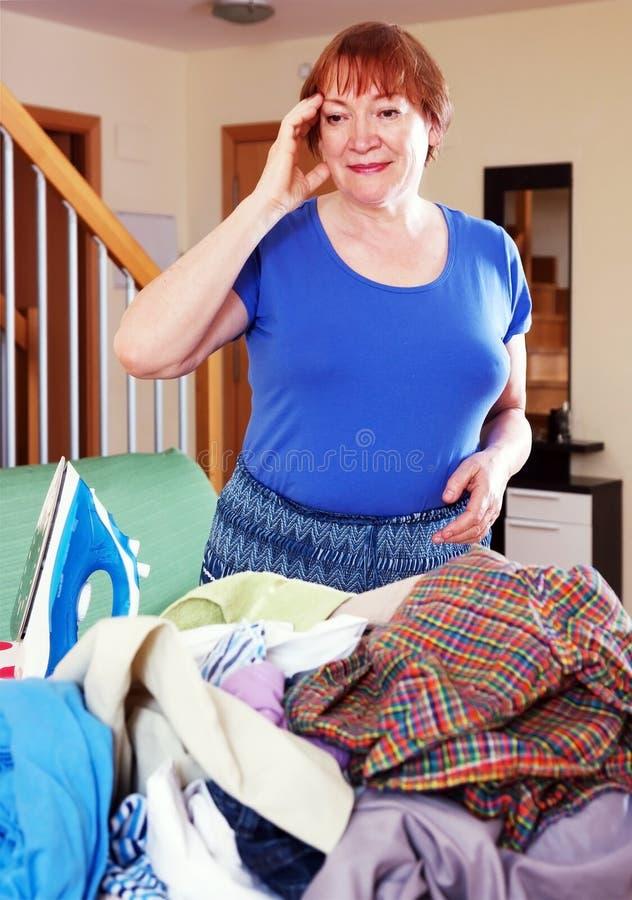De vermoeide vrouw strijkt kleren royalty-vrije stock afbeelding