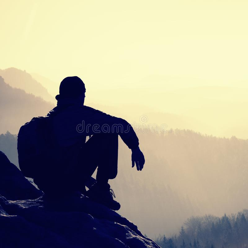 De vermoeide wandelaar met sportieve rugzak zit op rotsachtige piek en het letten op in diepe nevelige valleiblaasbalg Zonnige de stock foto's
