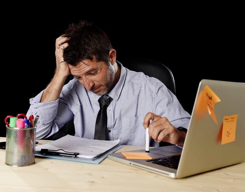 De vermoeide zakenman die het werk aan spanning lijden verspilde ongerust gemaakte bezig in bureau laat bij nacht met laptop comp stock afbeeldingen