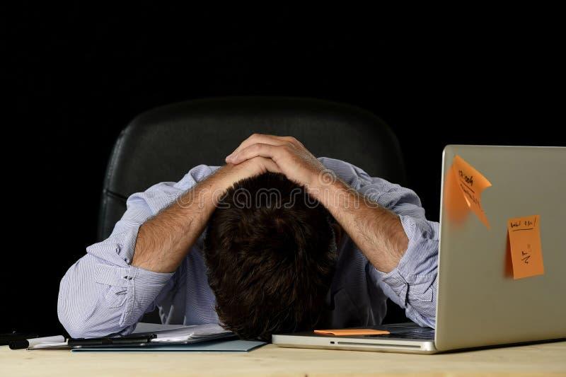 De vermoeide zakenman die het werk aan spanning lijden verspilde ongerust gemaakte bezig in bureau laat bij nacht met laptop comp royalty-vrije stock fotografie