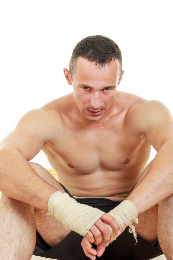 De vermoeide zitting die van de mensenvechter polsverbanden op zijn handen dragen stock afbeelding