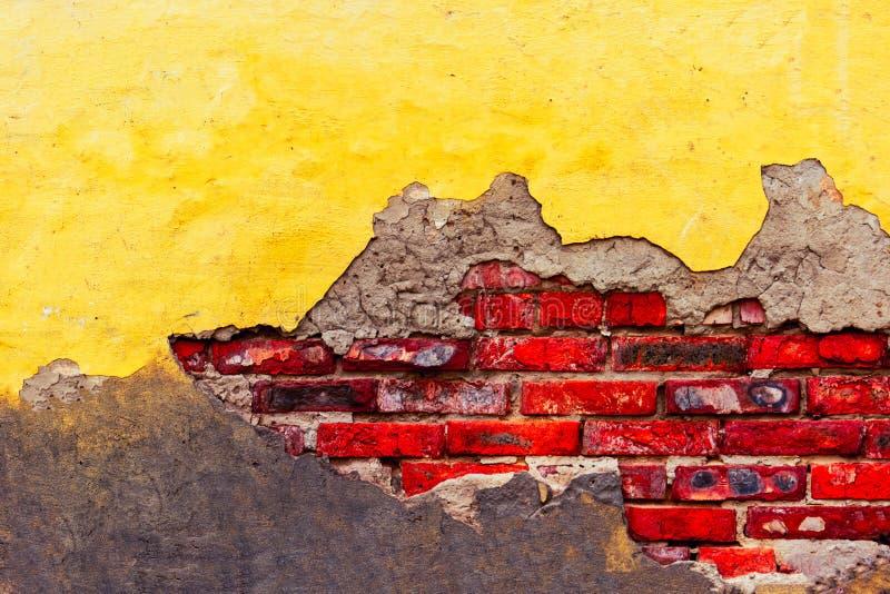 De verontruste bakstenen muur met barsten en het gebroken gele pleister vernietigden half muurdekking stock fotografie