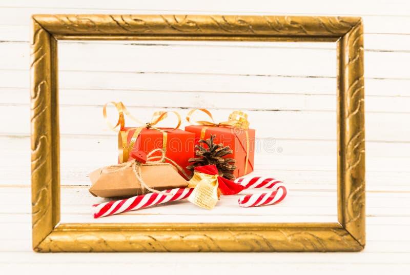 De verpakte giften of stellen en het rietsuikergoed op gouden fotokader voor stock afbeelding