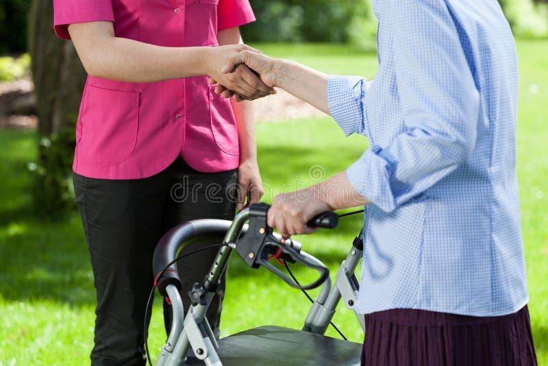 De verpleegster geeft hand ouder een vrouw stock fotografie