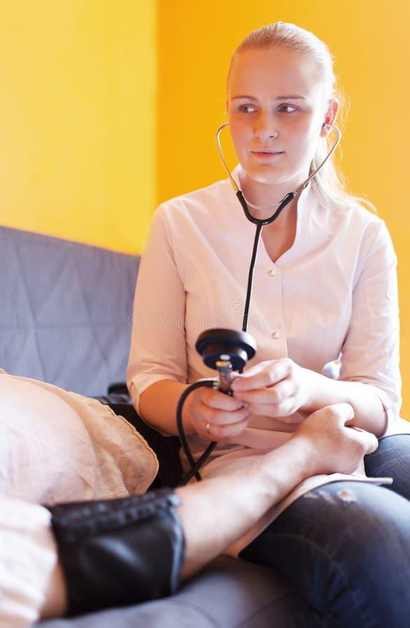 De verpleegster meet de geduldige bloeddruk stock afbeeldingen