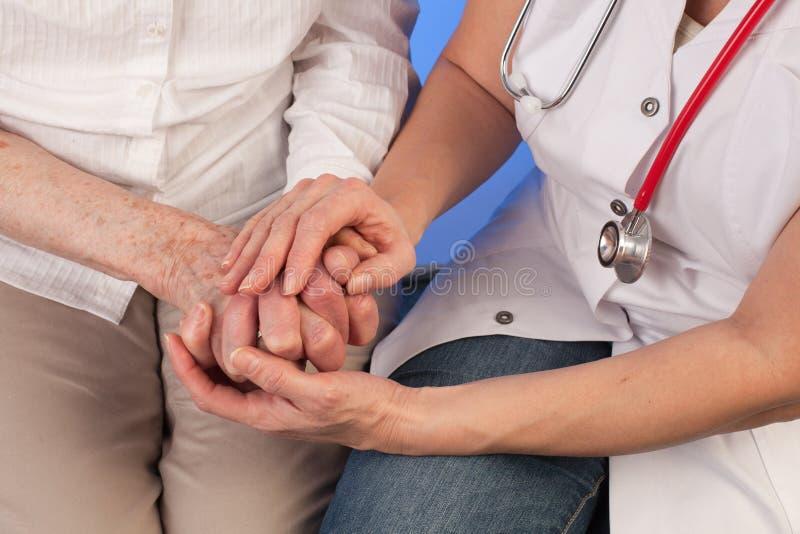 De verpleegster met stethoscoop houdt veel liefs handen van bejaarde stock fotografie