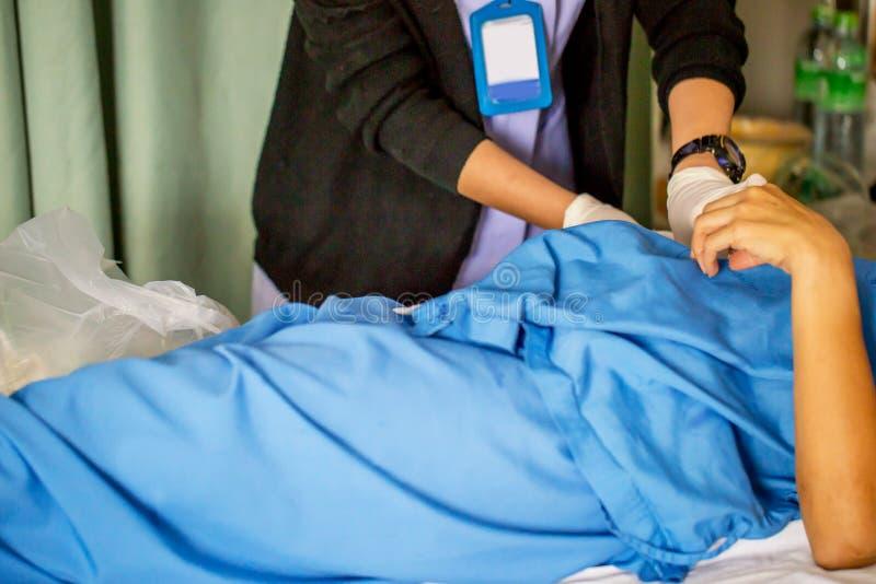 De verpleegster met veel geneeskunde bereidt of maakt de steek van haar vrouwenpatiënt na voor schoon chirurgie in de geduldige a royalty-vrije stock fotografie