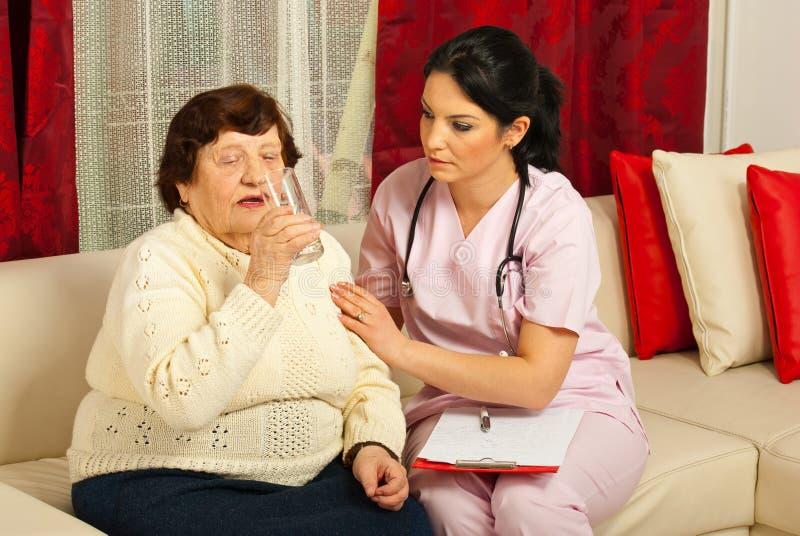 De verpleegster staat bejaard drinkwater bij royalty-vrije stock fotografie