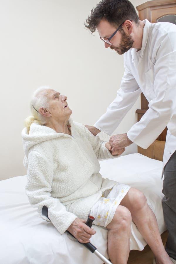 De verpleger helpt de oude grootmoeder om uit bed te krijgen stock foto's