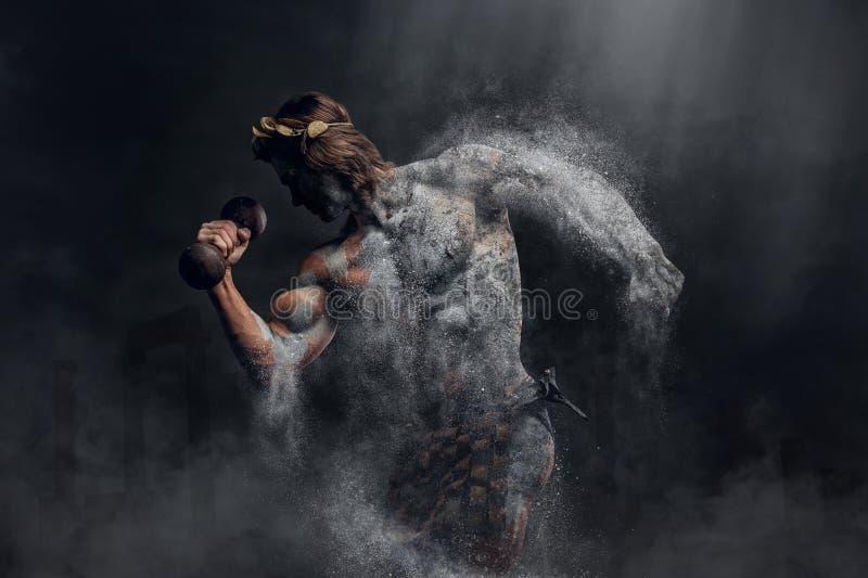 De verpletterende steen menselijke atleet houdt dumbbel stock foto