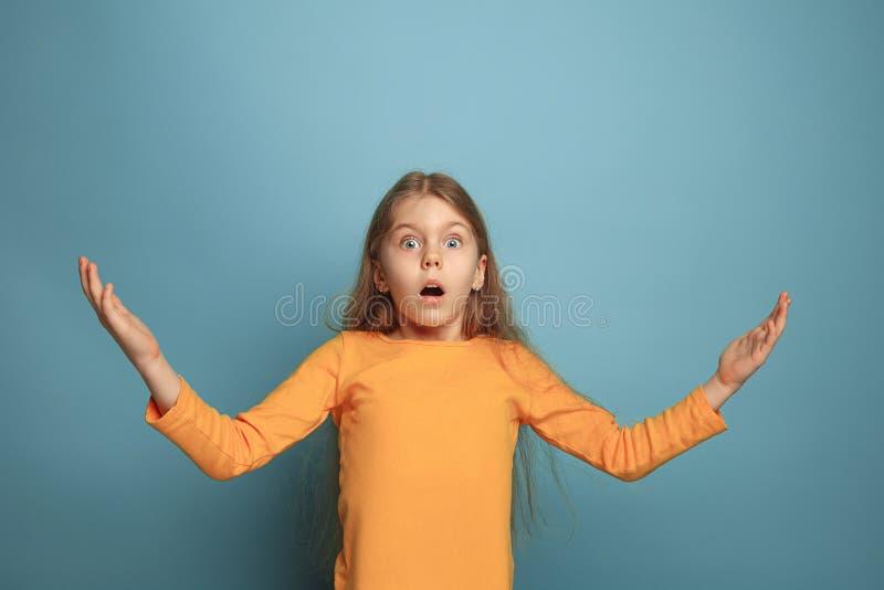 De verrassing, het geluk, de vreugde, de overwinning, het succes en het geluk Tienermeisje op een blauwe achtergrond Gelaatsuitdr stock afbeeldingen
