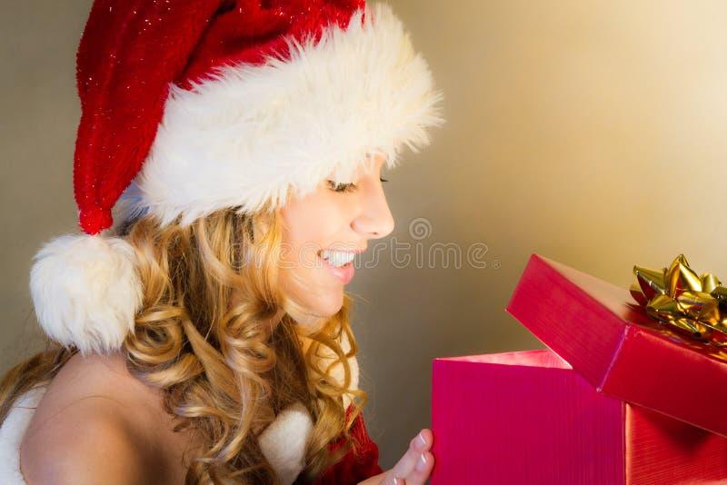 De verrassing van de vrouw wanneer het openen van Kerstmisgift stock foto