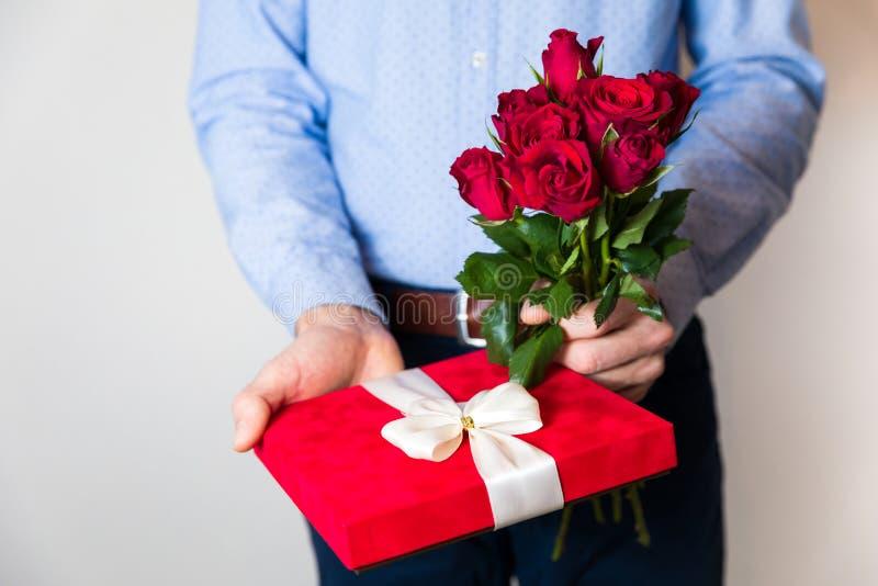 De verrassing van de valentijnskaartendag, liefde die, knappe mens romantische gift en rood rozenboeket houden royalty-vrije stock afbeeldingen