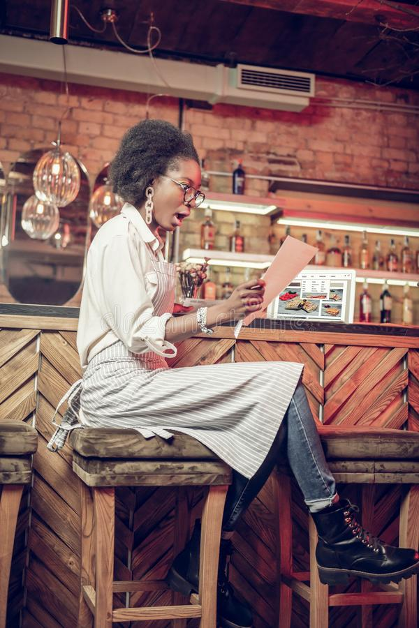 De verraste Afro-Amerikaanse donker-haired buitensporige barwerknemer die met glazen documenten bekijken dient binnen schok in stock afbeeldingen