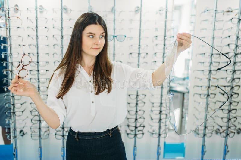 De verraste dame houdt reusachtige glazen in optische opslag royalty-vrije stock afbeeldingen