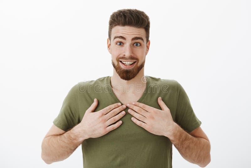 De verraste dankbare en verbaasde gelukkige jonge gebaarde kerel in olijft-shirt die wenkbrauwen opheffen verbaasde en wekte het  stock afbeeldingen