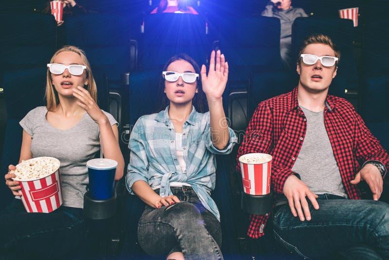De verraste en verbaasde mensen zitten als voorzitter in bioskoop Zij letten op film en bekijken het scherm met stock afbeeldingen