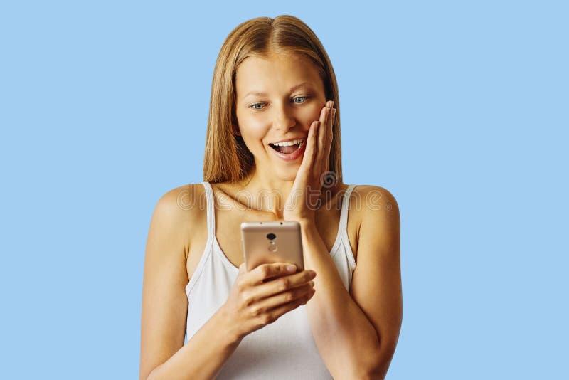 De verraste glimlachende vrouw houdt haar die smartphone, over blauwe achtergrond wordt geïsoleerd royalty-vrije stock foto's