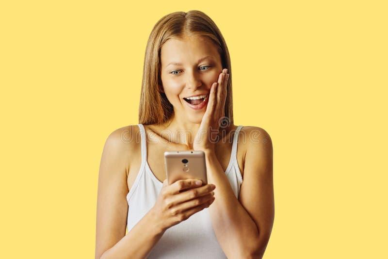 De verraste glimlachende vrouw houdt haar smartphone, over gele achtergrond royalty-vrije stock afbeelding