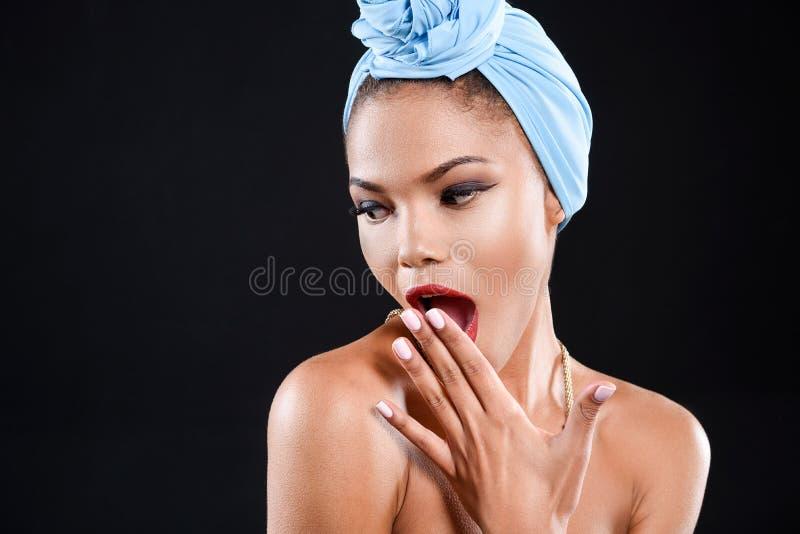 De verraste jonge vrouw kijkt neer stock afbeelding