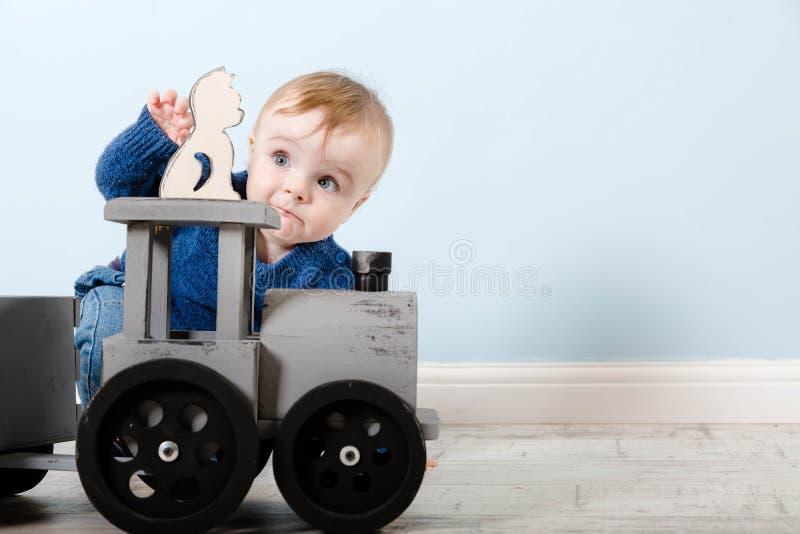 De verraste jongen blond in een blauwe sweater zit op een houten vloer ??n ??njarige baby het spelen met houten speelgoed Hij wil royalty-vrije stock afbeelding