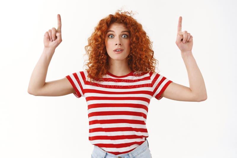 De verraste overweldigde geamuseerde adem van de de wijd open ogengreep van de roodharige aantrekkelijke krullend-haired vrouw he royalty-vrije stock foto's