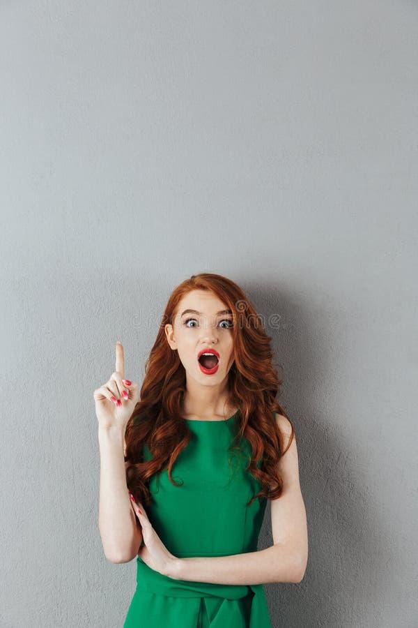 De verraste roodharige jonge dame in groene kleding heeft een idee royalty-vrije stock afbeelding