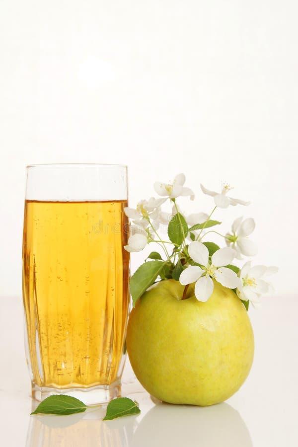De verre complètement du jus frais avec la pomme verte mûre photographie stock