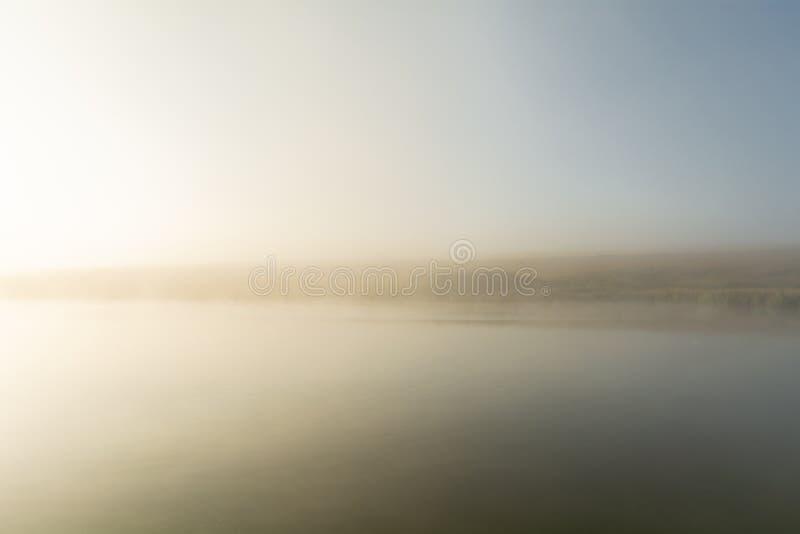 De verre kust van het meer is nauwelijks zichtbaar wegens de sterke ochtendmist bij dageraad Minimalismstijl royalty-vrije stock foto's