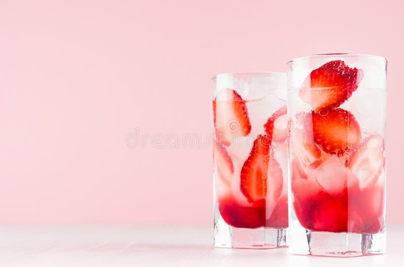 De vers fruitcocktail van aardbei misted binnen glas met ijsblokjes, snijdt bes en soda op elegante pastelkleur roze achtergrond stock afbeeldingen