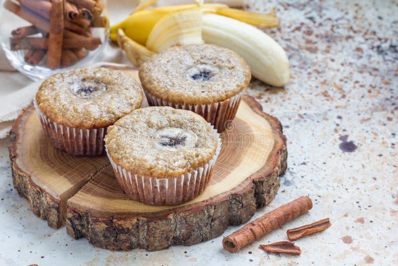 De vers gebakken eigengemaakte muffins van de banaankaneel met plak van banaan op bovenkant, op houten raad stock foto's