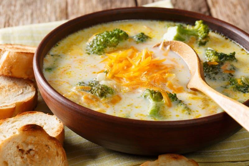 De vers gekookte soep van de broccolikaas in een kom met toost dicht-u stock afbeeldingen
