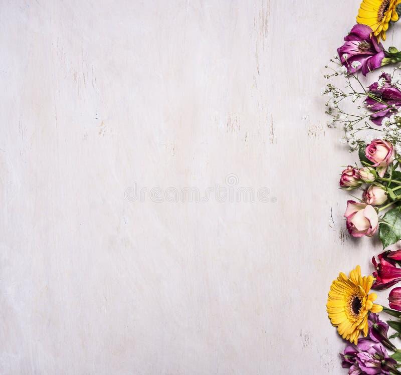 De verscheidenheid van de lente bloeit, gele rozen, de struikrozen, fresia, zonnebloemen, grens, plaats voor tekst op houten plat royalty-vrije stock foto