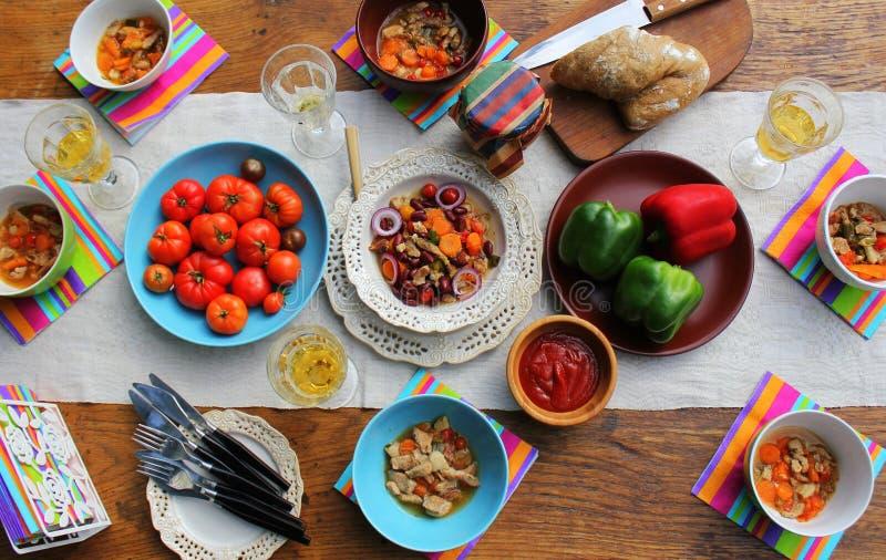 De verscheidenheid van het familiediner van maaltijdschotels met glas wijn op houten lijst diner lijst kaviaar en tafelkleed met  stock fotografie