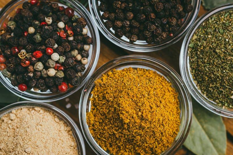 De verscheidenheid van kruiden in rond glas werpt - gemalen gember, hop-suneli, Kari, zwarte peper en een mengsel stock fotografie