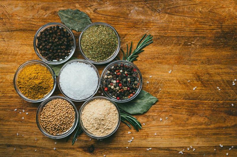 De verscheidenheid van kruiden in rond glas werpt - gemalen gember, hop-suneli, Kari, zwarte peper en een mengsel royalty-vrije stock foto