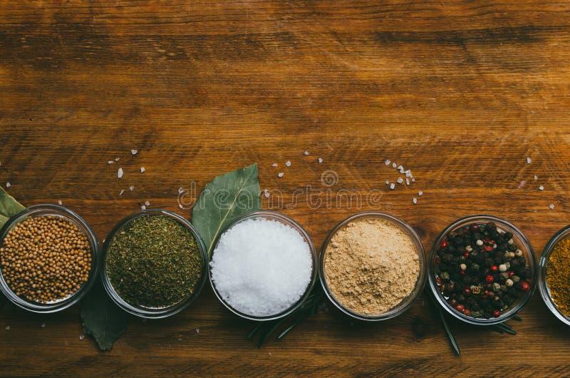 De verscheidenheid van kruiden in rond glas werpt - gemalen gember, hop-suneli, Kari, zwarte peper en mengeling stock afbeelding