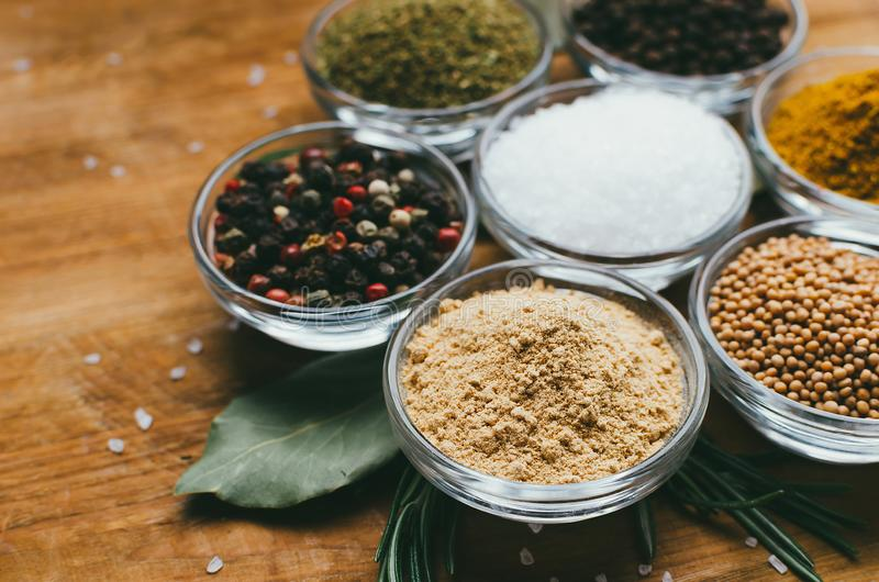 De verscheidenheid van kruiden in rond glas werpt - gemalen gember, hop-suneli, Kari, zwarte peper en mengeling stock foto's