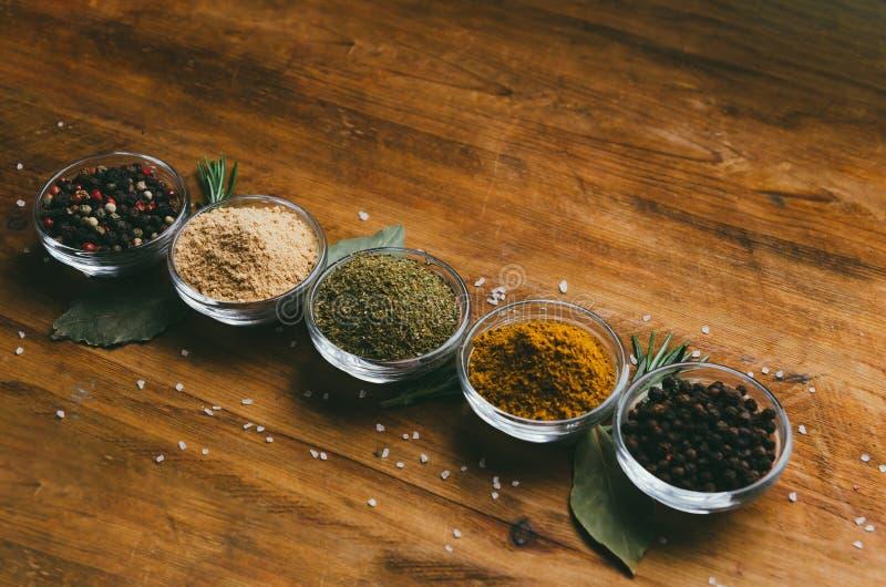 De verscheidenheid van kruiden in rond glas werpt - gemalen gember, hop-suneli, Kari, zwarte peper en mengeling royalty-vrije stock afbeeldingen
