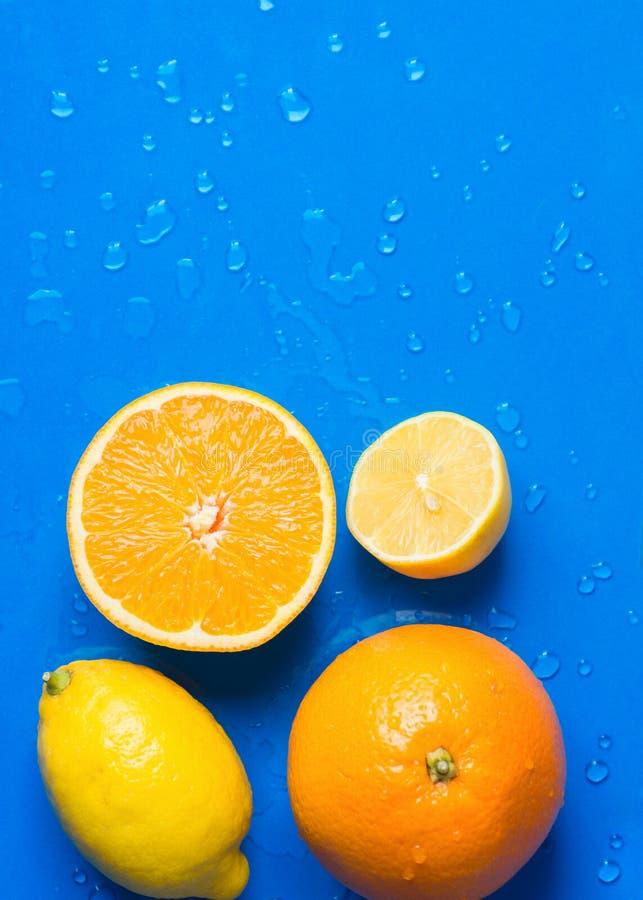 De verscheidenheid van rijpe organische citrusvruchten halveerde gehele sinaasappelen gesneden citroenen op blauwe achtergrond me royalty-vrije stock afbeelding