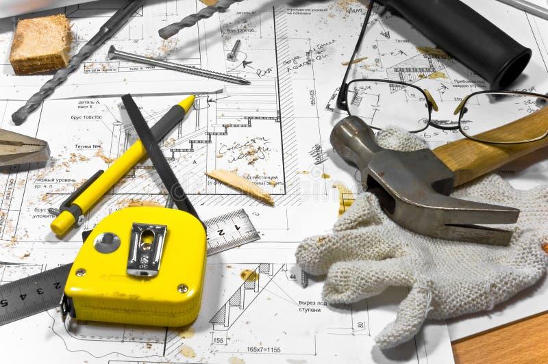 De verschillende hulpmiddelen liggen op timmermanswerkbank. stock afbeeldingen