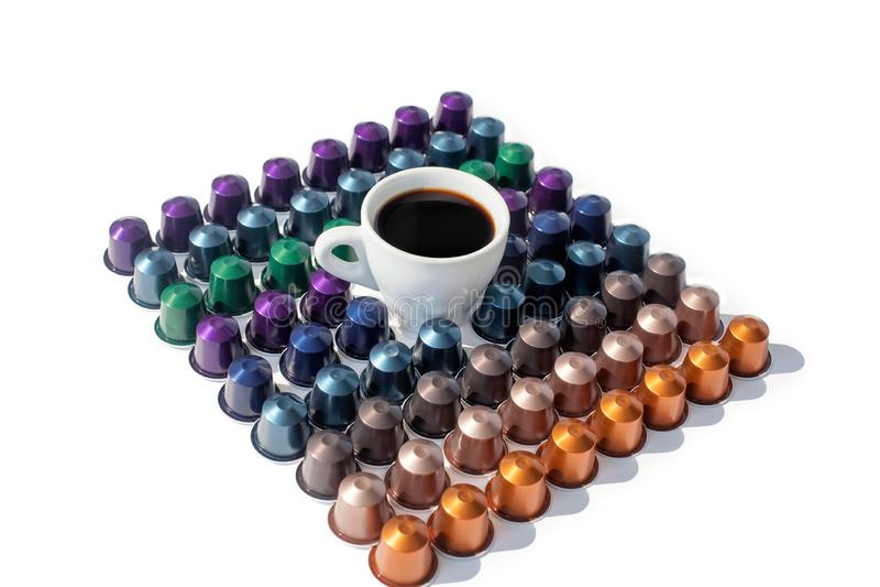De verschillende kleuren van koffiecapsules en witte kop van hete zwarte koffie op witte geïsoleerde achtergrond royalty-vrije stock foto's