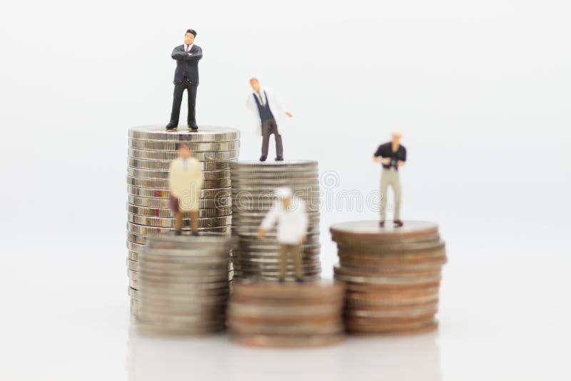 De verschillende mensen die zich op stapelmuntstukken bevinden, die als salarissen gebruiken zijn verschillend van vele beroepenc stock foto