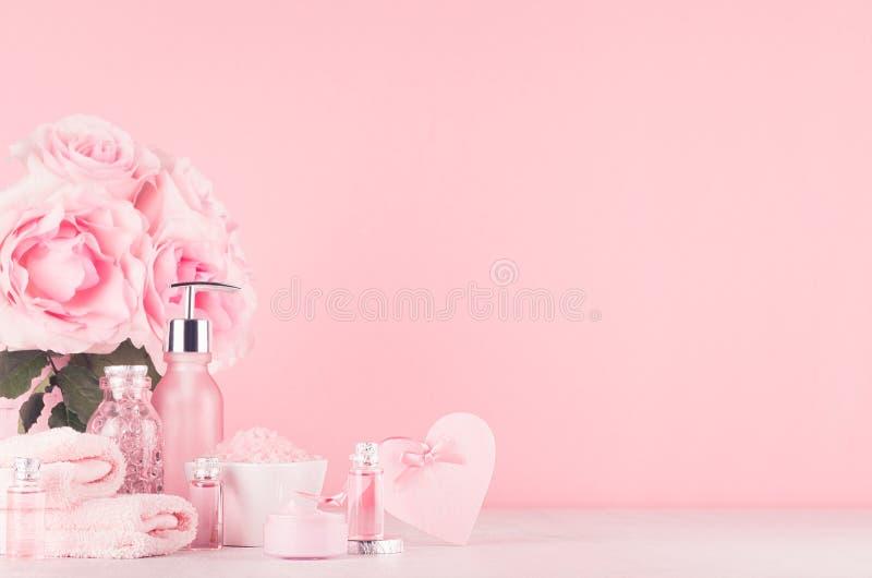 De verschillende producten van de huidzorg met romantisch rozenboeket, decoratief hart op meisjesachtige elegante roze pastelkleu stock fotografie