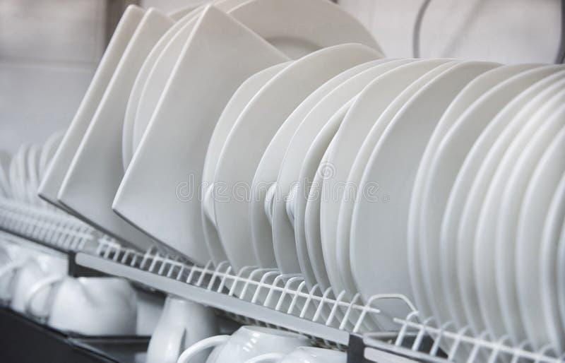 De verschillende witte schone platen en de koppen drogen op een plank royalty-vrije stock afbeeldingen