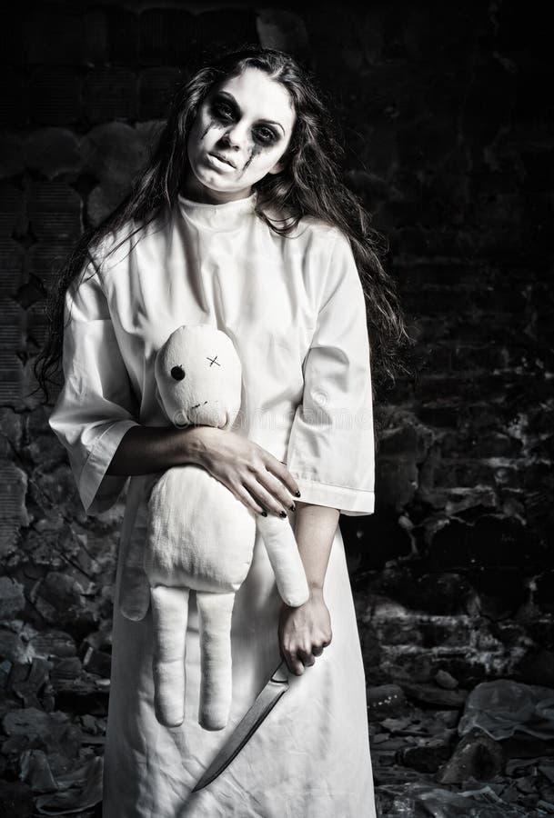 De verschrikking schoot: eng monstermeisje met moppetpop en mes in handen royalty-vrije stock foto's