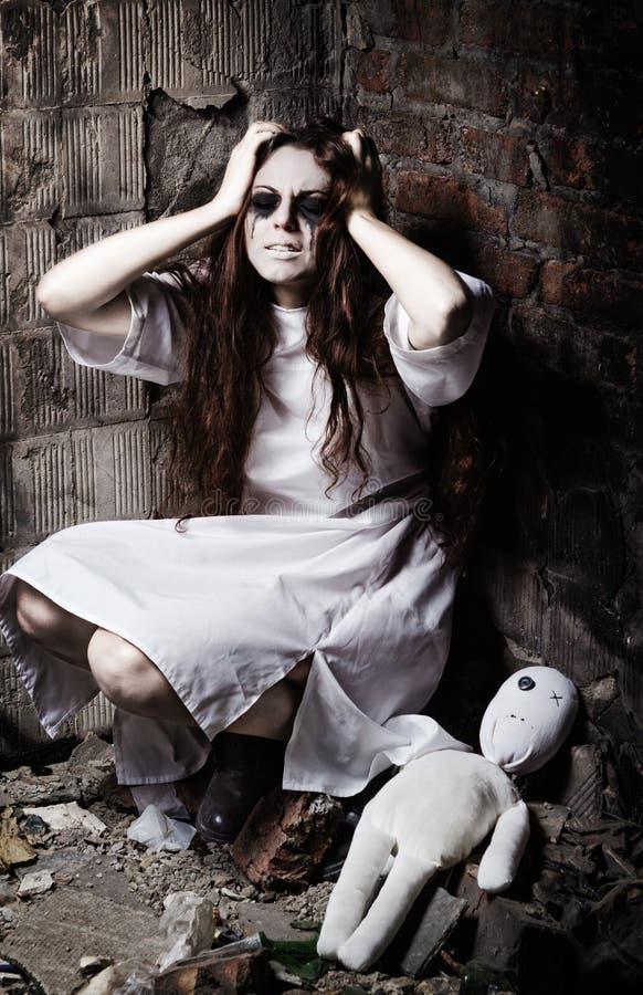 De verschrikkingsstijl schoot: vreemd gek meisje en haar moppetpop stock afbeelding